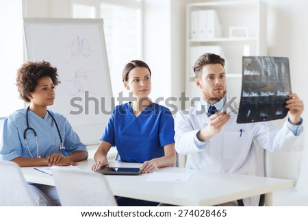 radiology, people and medicine concept - group of doctors looking to and discussing x-ray image at hospital - stock photo