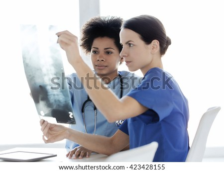 radiology, surgery, health care, people and medicine concept - female doctors or nurses looking to and discussing x-ray image of spine at hospital
