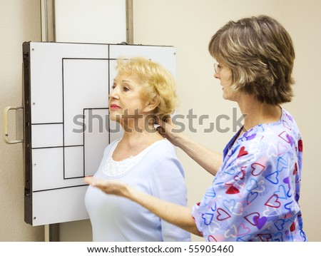 Radiology technician positions a patient to have x-rays taken. - stock photo