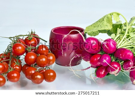 Radish and cherry tomatoes on a glass table, on a white background - stock photo