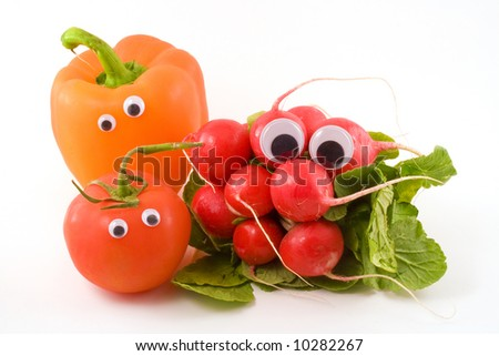 Radishes,a tomato and an orange bell pepper with googly eyes sit on a white background. - stock photo