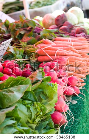 Radishes amidst other vegetables at the farmer's market. Shallow depth of field, focus on radishes. - stock photo