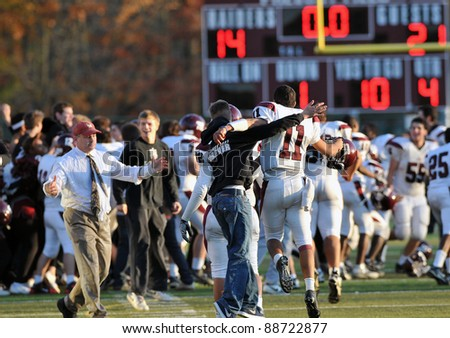 RADNOR, PA - NOVEMBER 12: Players and fans celebrate a Lower Merion 21-14 win over in the 115th meeting of the two schools in football, the longest rivalry in the US, November 12, 2011 in Radnor, PA. - stock photo