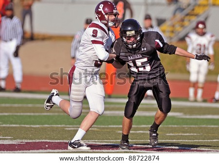 RADNOR, PA - NOVEMBER 12: Radnor's Ellis Schaefer (#15) is blocked on kick coverage during the 115th meeting of Radnor and Lower Merion High School football teams November 12, 2011 in Radnor, PA - stock photo
