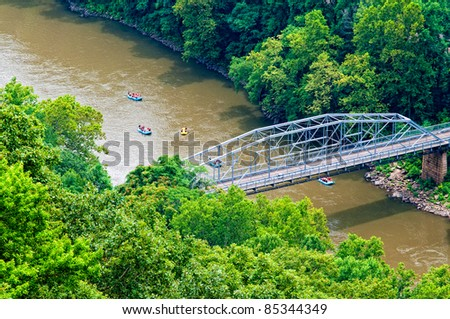 Rafters on the New River in West Virginia with a bridge - stock photo