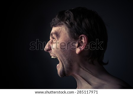 Rage. Shouting young man. Tense face. Side view. - stock photo