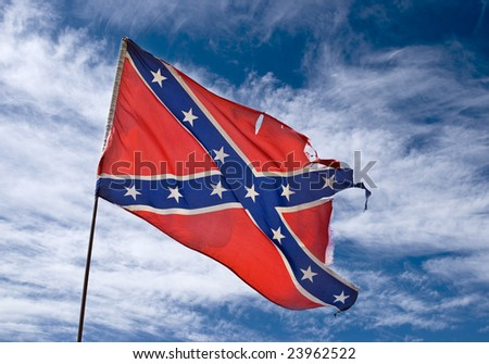 ragged confederate flag flying against sky - stock photo