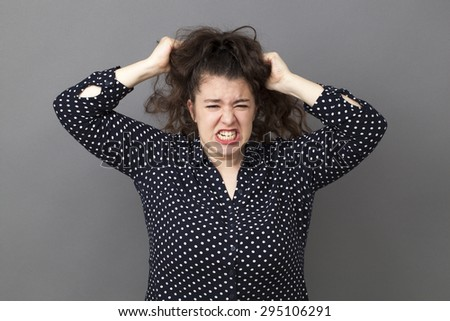 raging overweight 20's woman losing temper, tearing hair out for exasperation and frustration - stock photo
