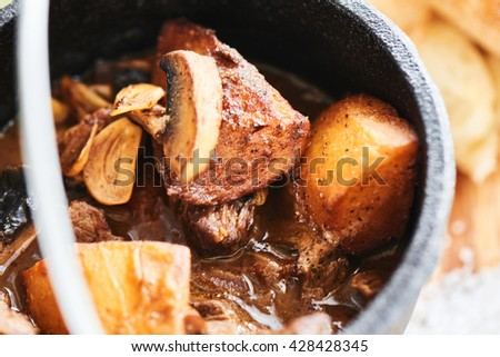 Ragout of veal with mushrooms, sauce demiglas in an iron pot  closeup