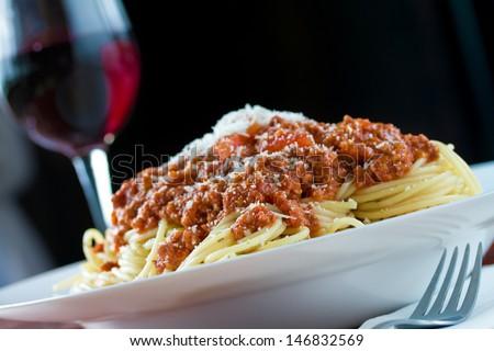 Ragu alla bolognese a complex sauce with spaghetti pasta and glass of red wine - stock photo