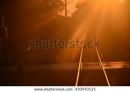 Rail of train lighted in last sunset light. Beautiful calm summer wallpaper as a sign of love to traveling