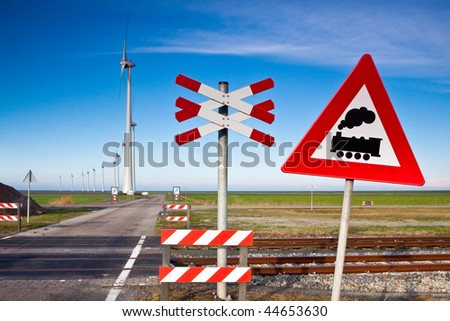 Rail road sign with windmills on the background