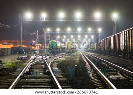 Rail yard with railroad cars and cisterns. Night view - stock photo