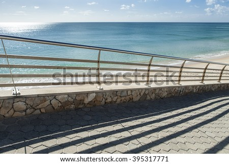 Railing aside a pathway near a beach, casting a shadow on the ground