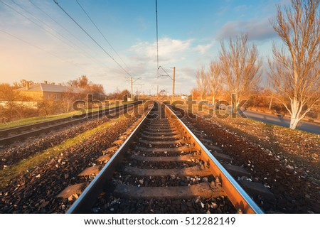 Railroad against beautiful sky at sunset. Industrial landscape with railway station, colorful blue sky, trees and grass, yellow sunlight. Railway junction. Heavy industry. Railways. Cargo shipping
