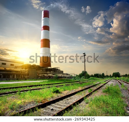 Railroad and industrial tube under cloudy sky - stock photo