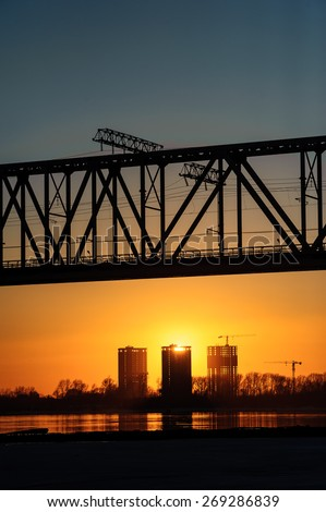 Railroad bridge and construction site on river bank in the sunset