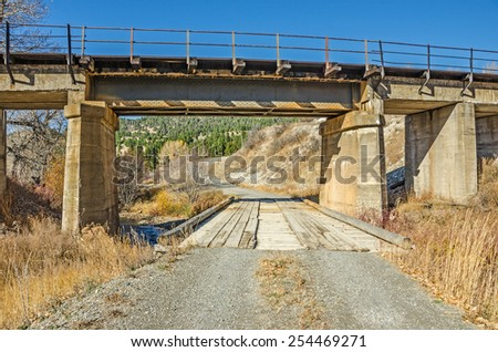 Railroad bridge over a gravel road and a wooden bridge that spans a creek - stock photo
