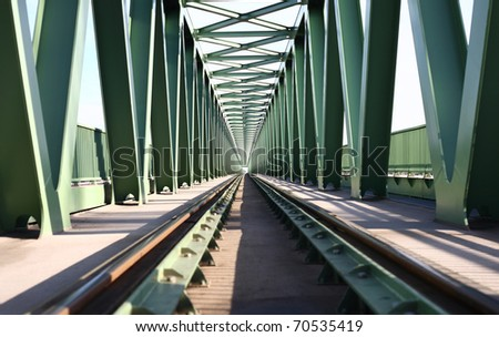 Railroad bridge with symmetrical metal structure and tracks. - stock photo