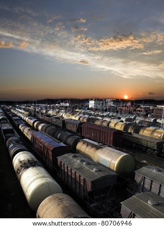 Railroad cars on a railway station. Cargo transportation. Work of industry. Urban scene. Beautiful sunset. - stock photo