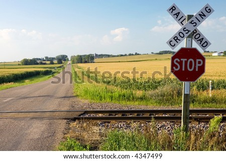 Railroad crossing and stop sign in farmland - stock photo