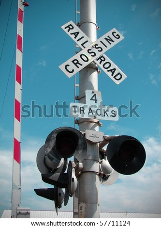 railroad crossing gate with blue sky - stock photo