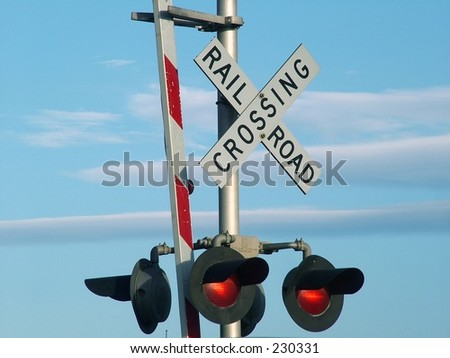 Railroad Crossing sign against blue sky with clouds - stock photo