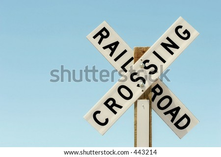 railroad crossing sign on wood against a light, clear blue sky