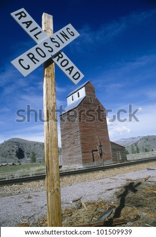 Railroad crossing sign with grain silo in background, Montana - stock photo