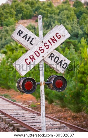 Railroad Crossing sign with tracks & trees in the distance. Shallow focus on the sign. - stock photo
