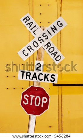 Railroad crossing stop sign against a yellow train car. - stock photo