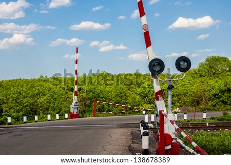 railroad crossing with a barrier - stock photo