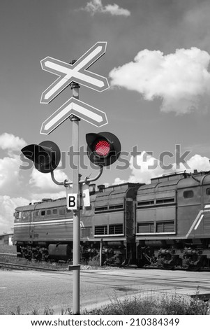Railroad crossing with passing freight train - black and white with a red signal light - stock photo