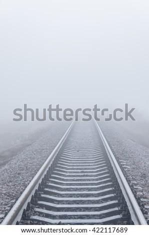 railroad goes to horizon in fog - stock photo