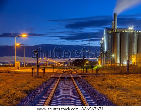 Railroad in a heavy Industrial Chemical area with mystical dreamy colors and lights in twilight - stock photo