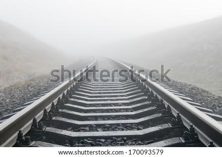 railroad in fog - stock photo