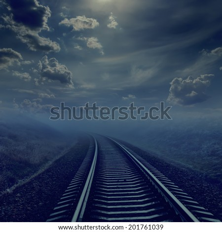 railroad in night to horizon in fog. moonlight in cloudy sky - stock photo