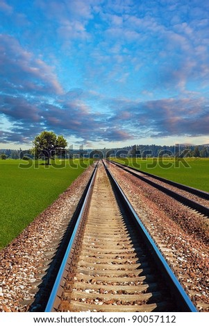 Railroad in the field on beautiful day - stock photo