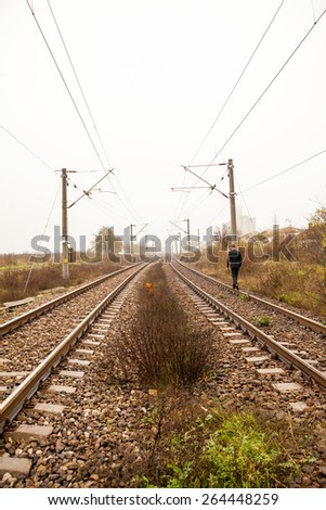Railroad in the field with person passing by - stock photo