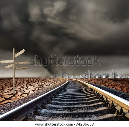 Railroad leading to desert storm, city in background - stock photo