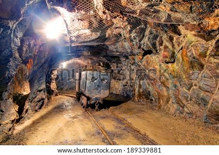 Railroad mine tunnel in a dark underground - stock photo