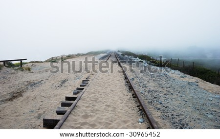 Railroad near California coast disappearing in the Fog. - stock photo
