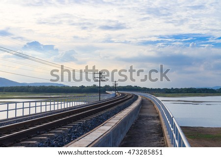 Railroad on the reservoir at Pasuk River Dam in summer, Lopburi, Thailand.