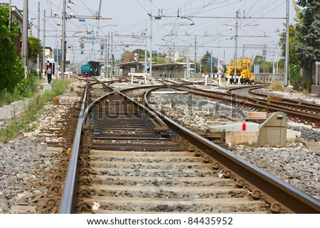 railroad rails with points, train at station and electric line - italian state railways - stock photo