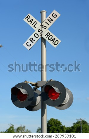 Railroad sign post during daytime with red light on