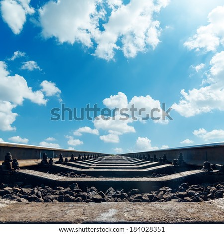 railroad to horizon and clouds in blue sky - stock photo