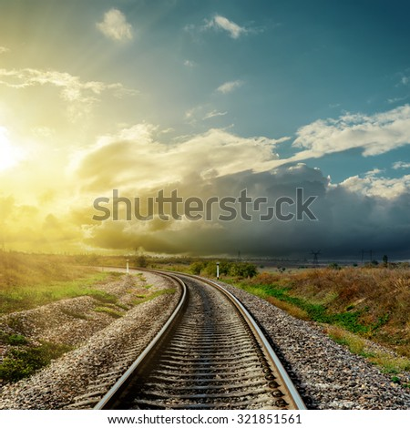 railroad to horizon and sunset in clouds - stock photo