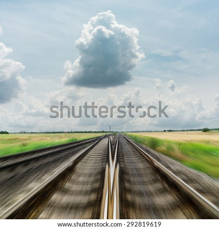 railroad to horizon in dramatic clouds. motion effect - stock photo