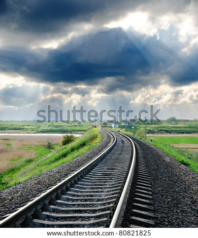 railroad to horizon under cloudy sky