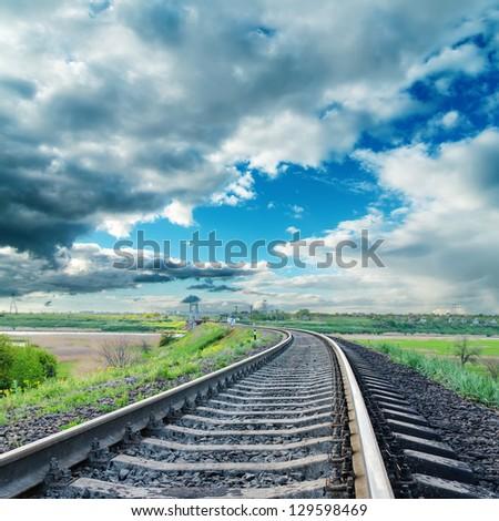railroad to horizon under dramatic sky - stock photo